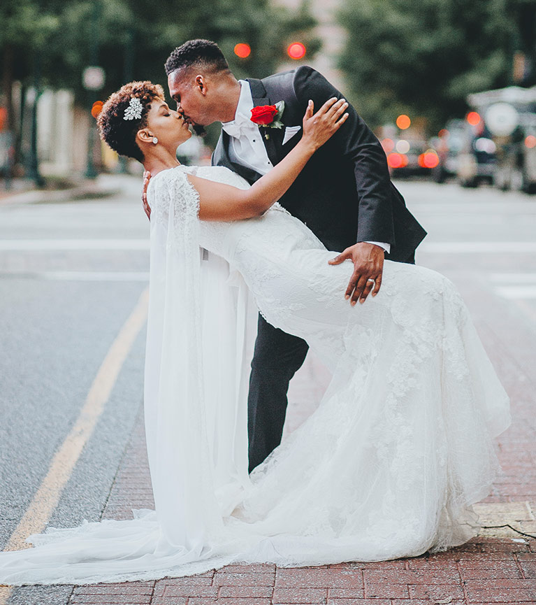 Groom dipping and kissing bride in the street