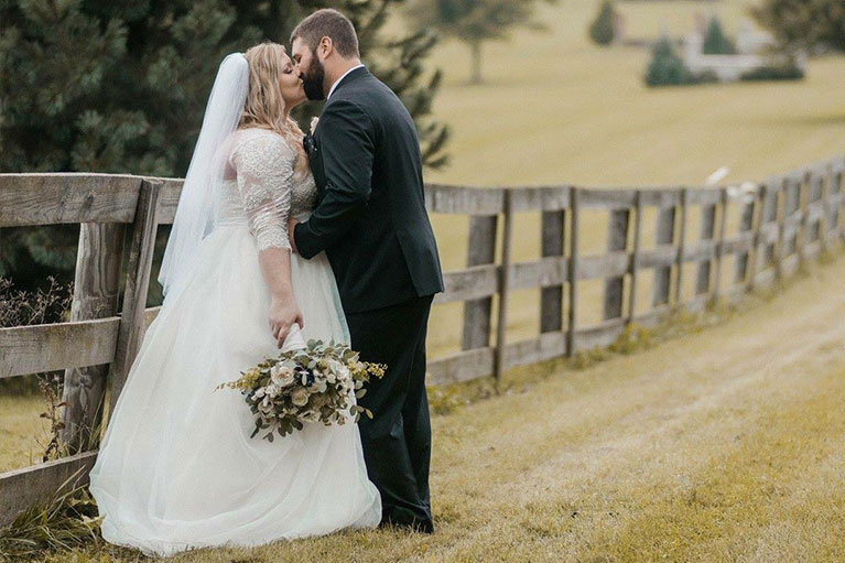 Bride and Groom kissing against farm fence in field