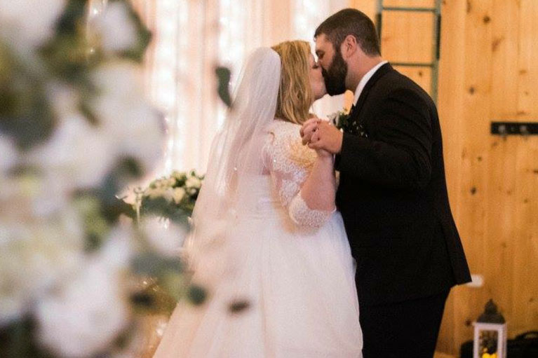 Bride and groom holding both hands and kissing
