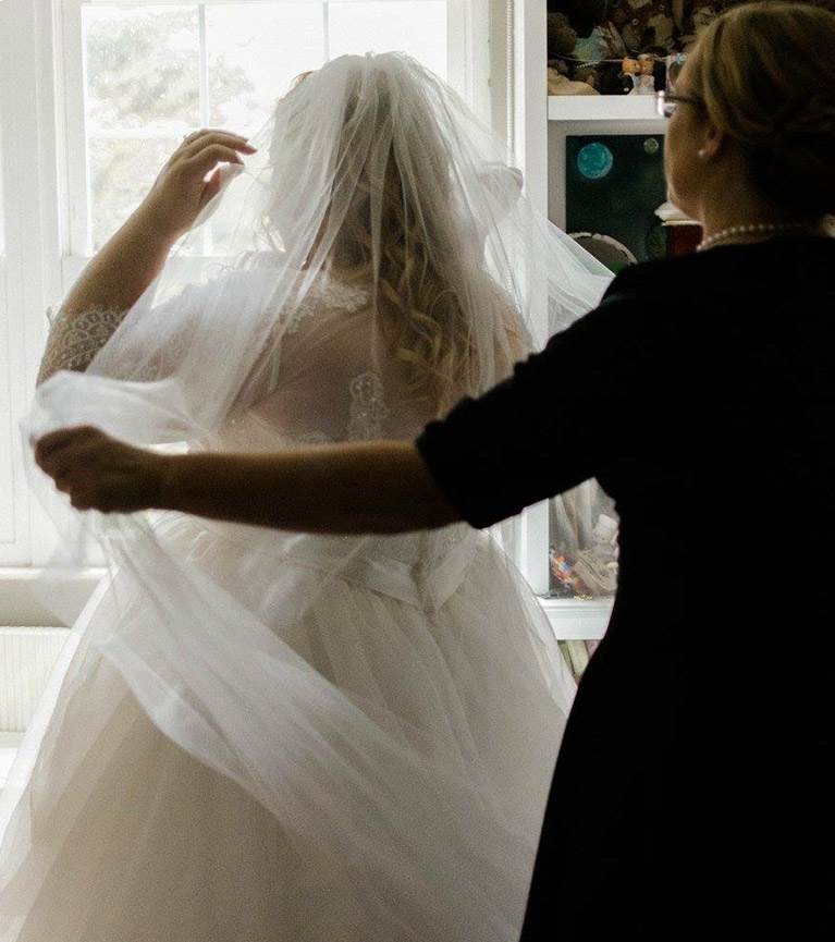 Wedding guest helping bride with veil