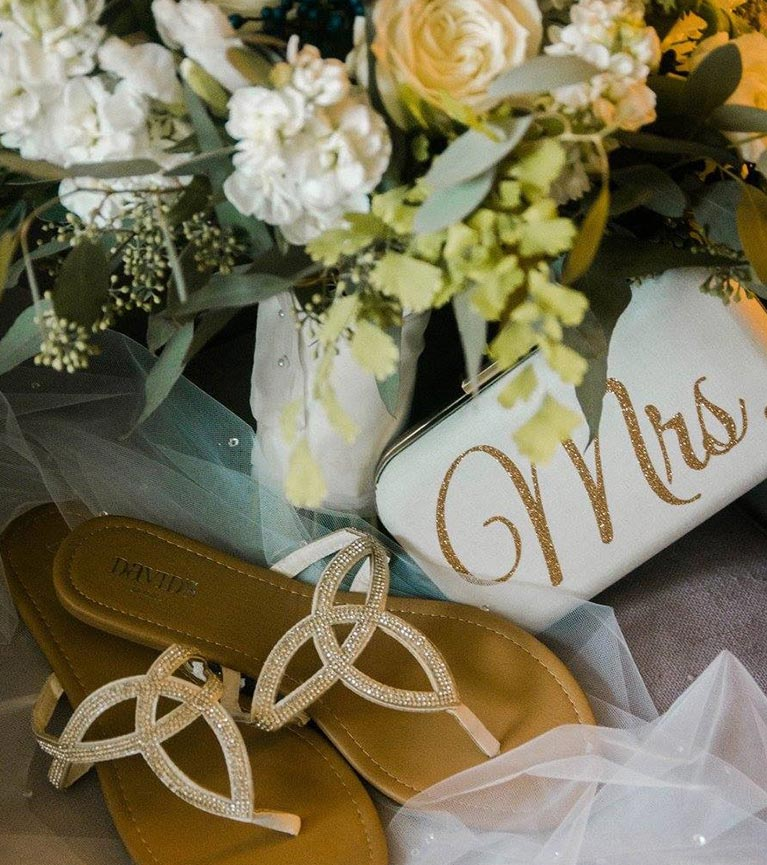 Bride sandals and Mrs clutch by bouquet of flowers and tulle