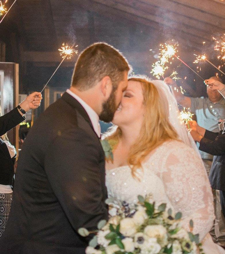 Bride and groom kissing while guests hold sparklers