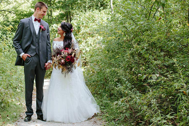 Romantic Fall Wedding | Newlyweds holding hands while  gazing into eachothers eyes