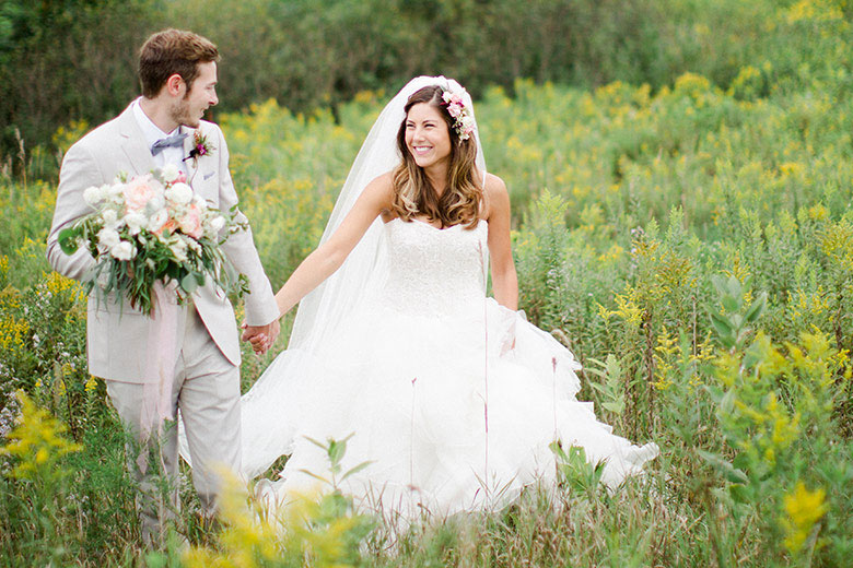 Rustic Summer Wedding | Newlyweds holding hands in the open field