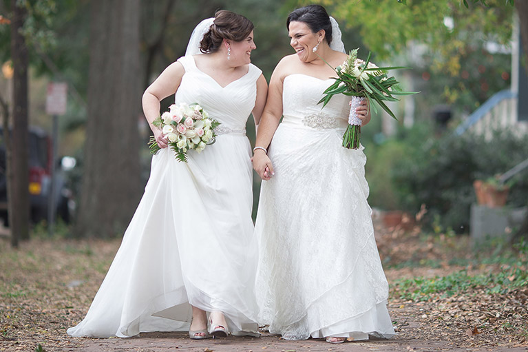 Two brides walking outdoors holding hands