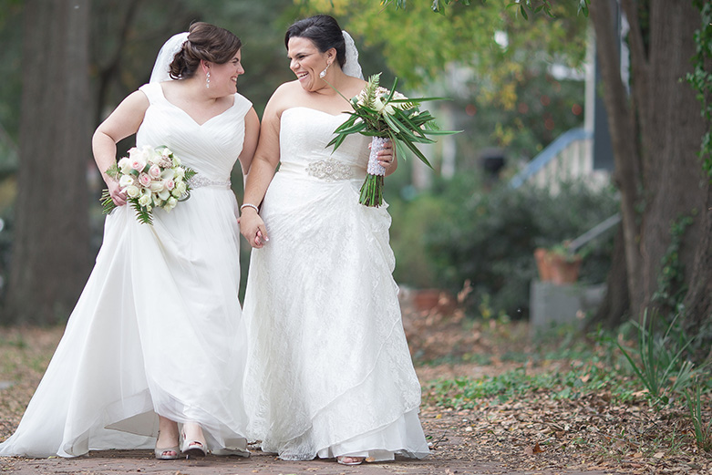Brides walking down street holding hands and smiling at each other