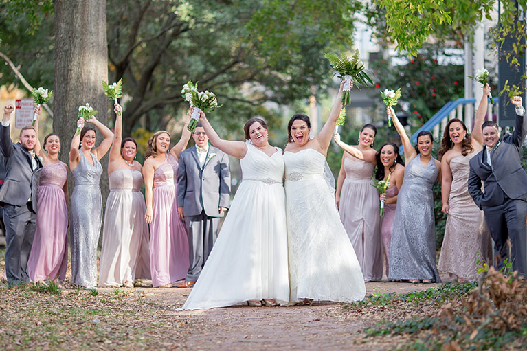 Brides and bridal party throwing hands up in the air