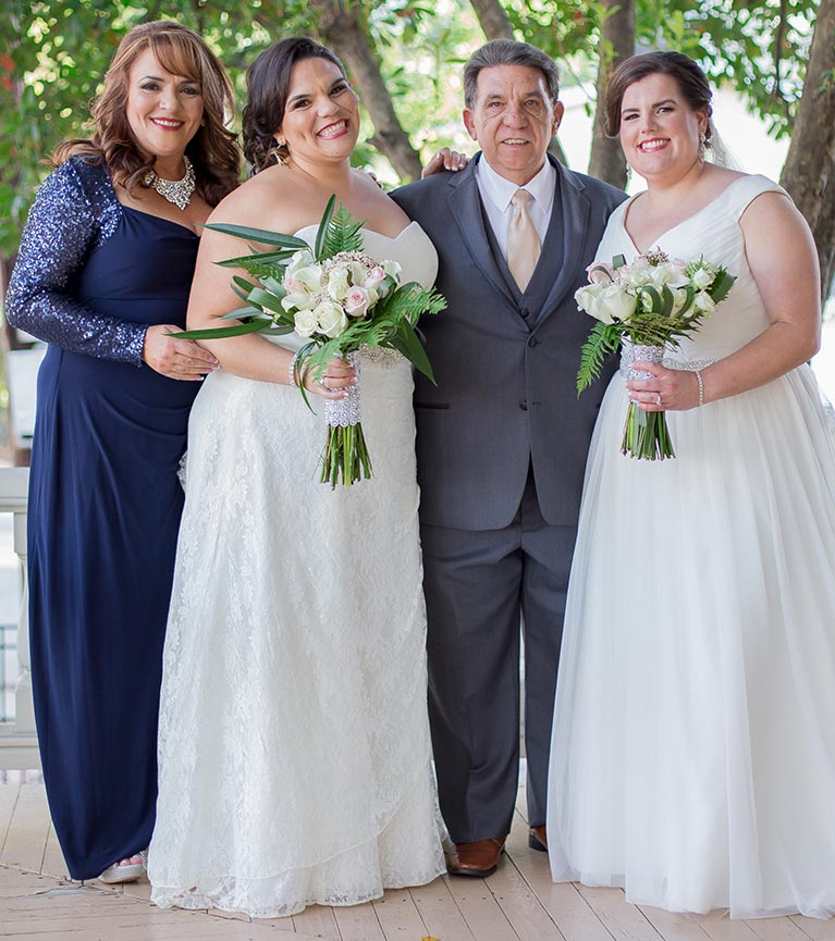 Brides posing with parents on wedding day