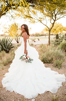 Bride posing outdoors with her wedding gown