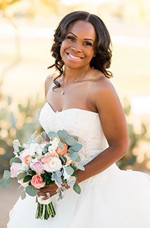 Bride posing with a smile while holding a bouqet