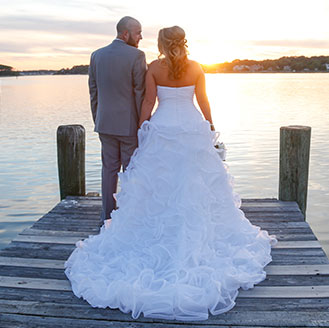 Newlyweds staring at eachother as the sunsets by the dock