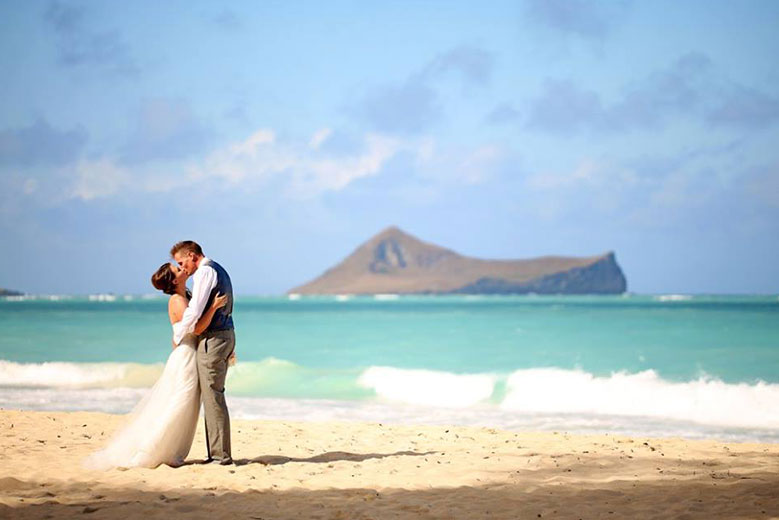 Newlyweds kissing on beach