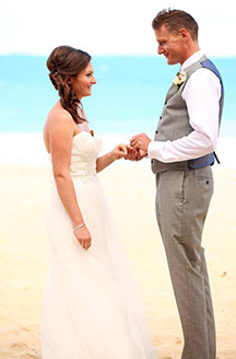 Husband placing the ring on his wife on the beach