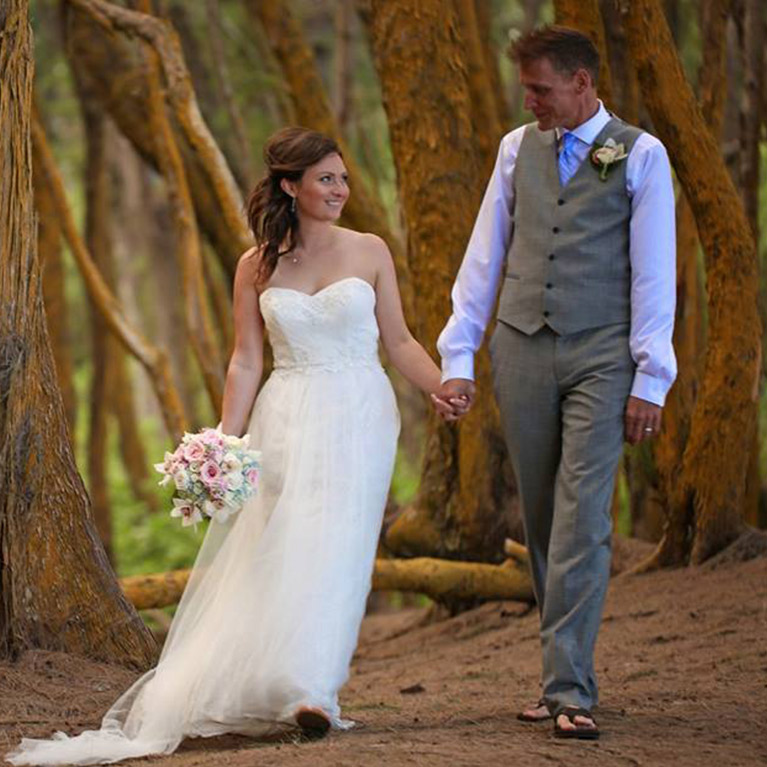Newlyweds holding hands while walking through the woods
