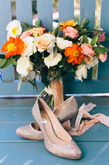 Gold shoes staged with flower bouquet
