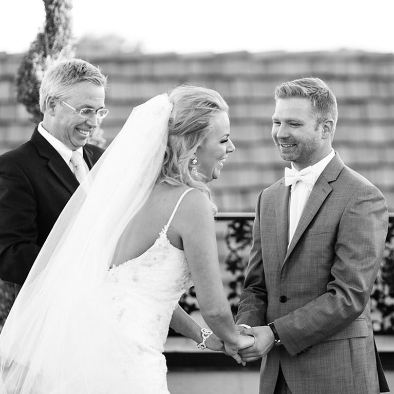 Black and white image of the newlyweds smiling at the alter