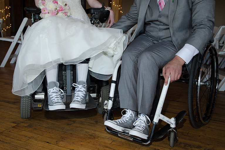 Close up of bride and groom in wheelchairs wearing matching sneakers