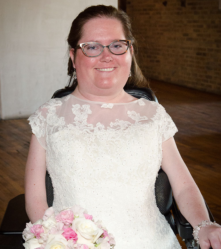 Bride wearing glasses and holding bouquet