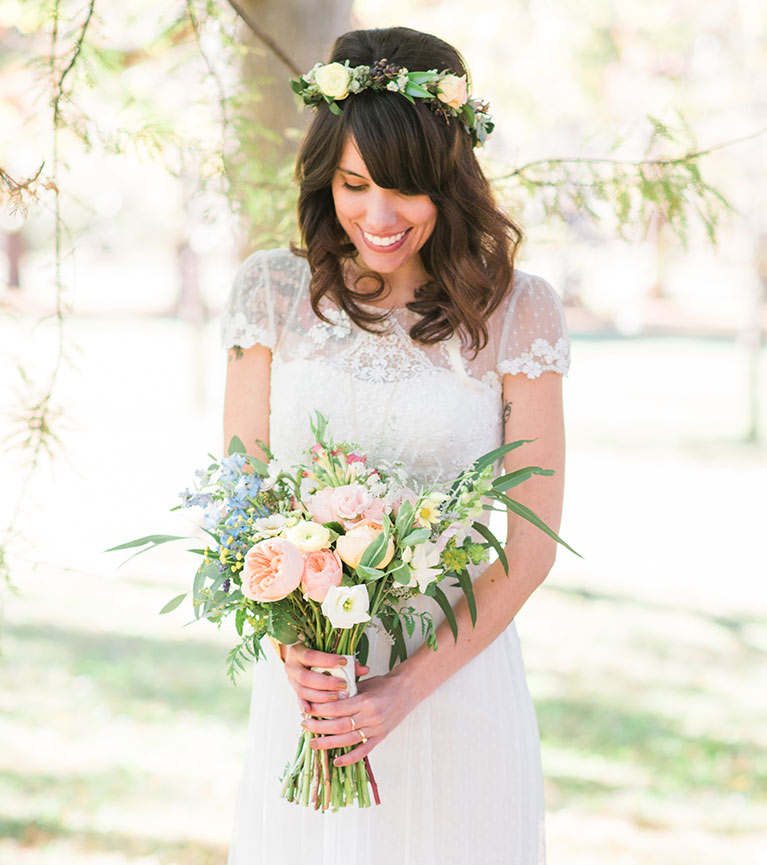 Bride with flower crown smiling at bouquet of flowers