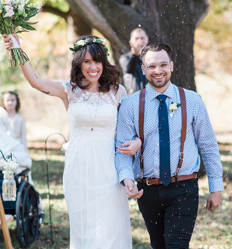 Newly wedded bride and groom walk down the aisle while bride holds bouquet in air