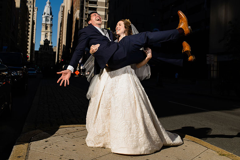 Bride holding up groom on city street