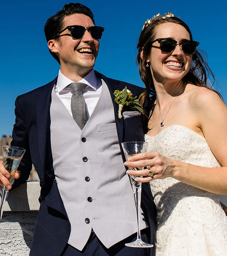 Bride and groom drinking champagne and wearing sunglasses