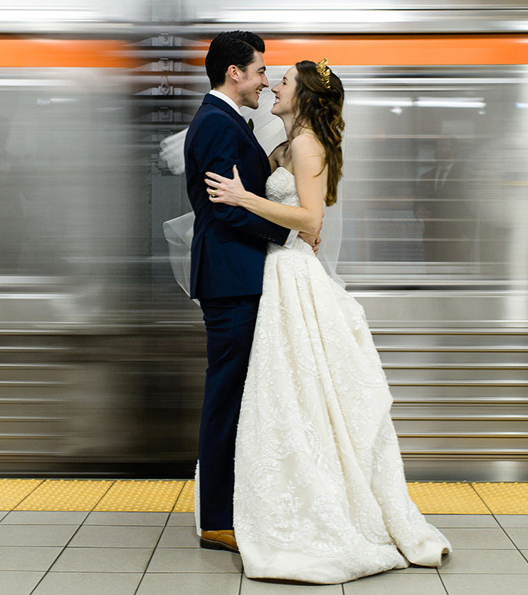 Bride and groom embracing by moving subway cars