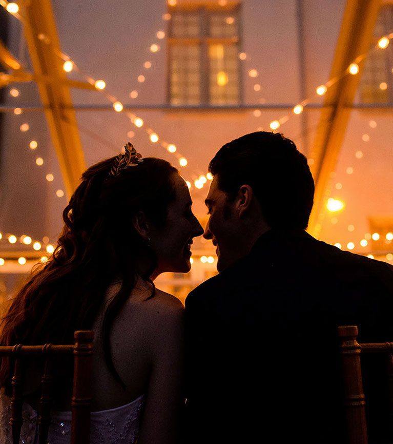 Bride and groom leaning in for a kiss by string lights