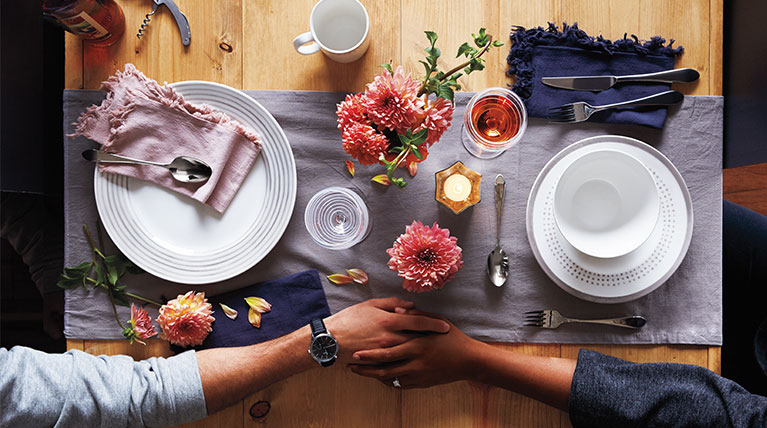 Man and woman holding hands at the dinner table with dinnerware and flowers