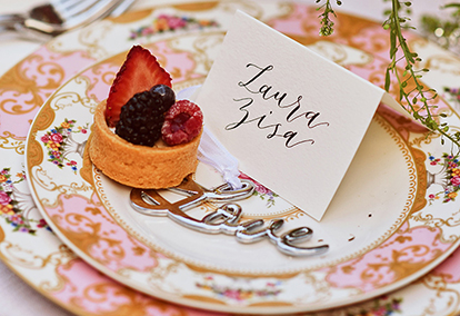 wedding china set up for a wedding with a placecard, dessert and silver 'love' ornament