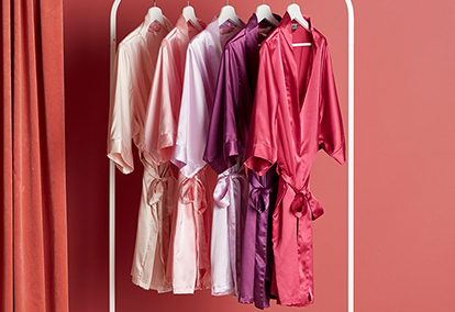 Pink robes of varying colors hanging on a rack