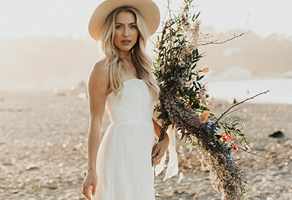 Bride in casual strapless dress with tan hat and bouquet standing on the beach