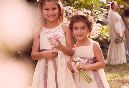 Flower girls wearing ivory dresses with color sashes at outdoor wedding