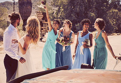 Bridesmaids standing in front of bride and groom in mis-matched bridesmaid dresses