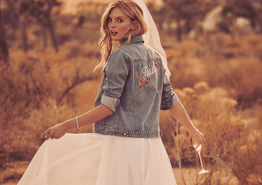 Bride walking through desert wearing Bridal Gown with jean jacket.