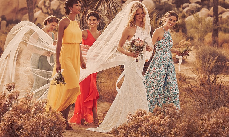 Bride with long flowing veil and colorful bridesmaids walking in desert