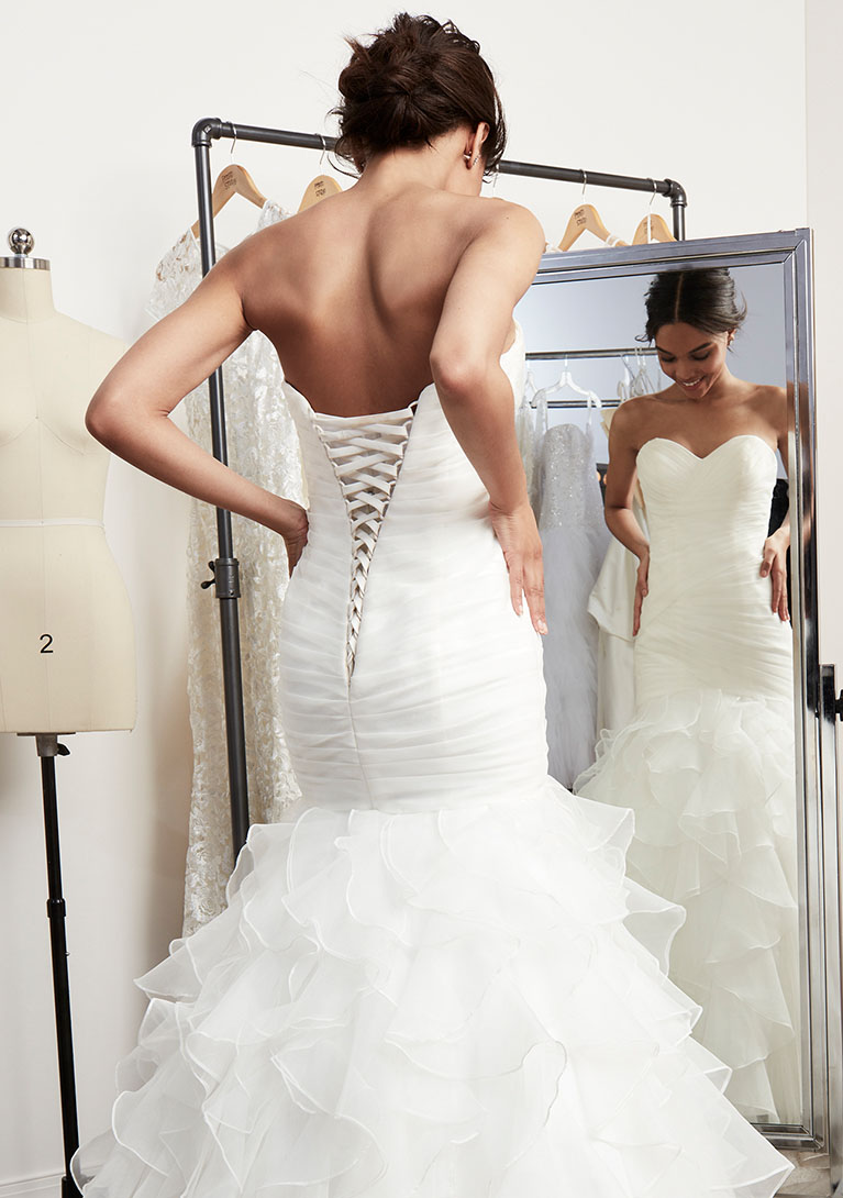 bride in alterations having corset added to wedding gown