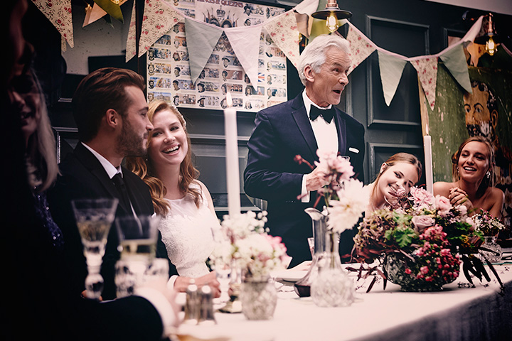 Father speaking while couple and guests laugh around the table