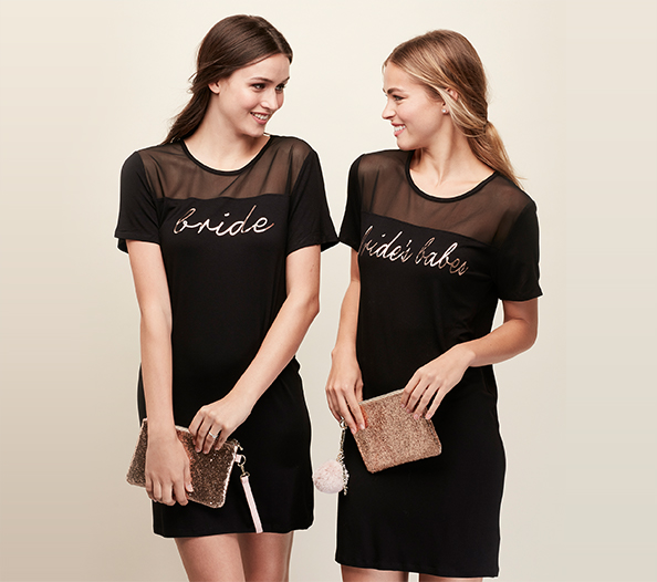 Bride and bridesmaid wearing matching black mini dresses holding glitter pouches