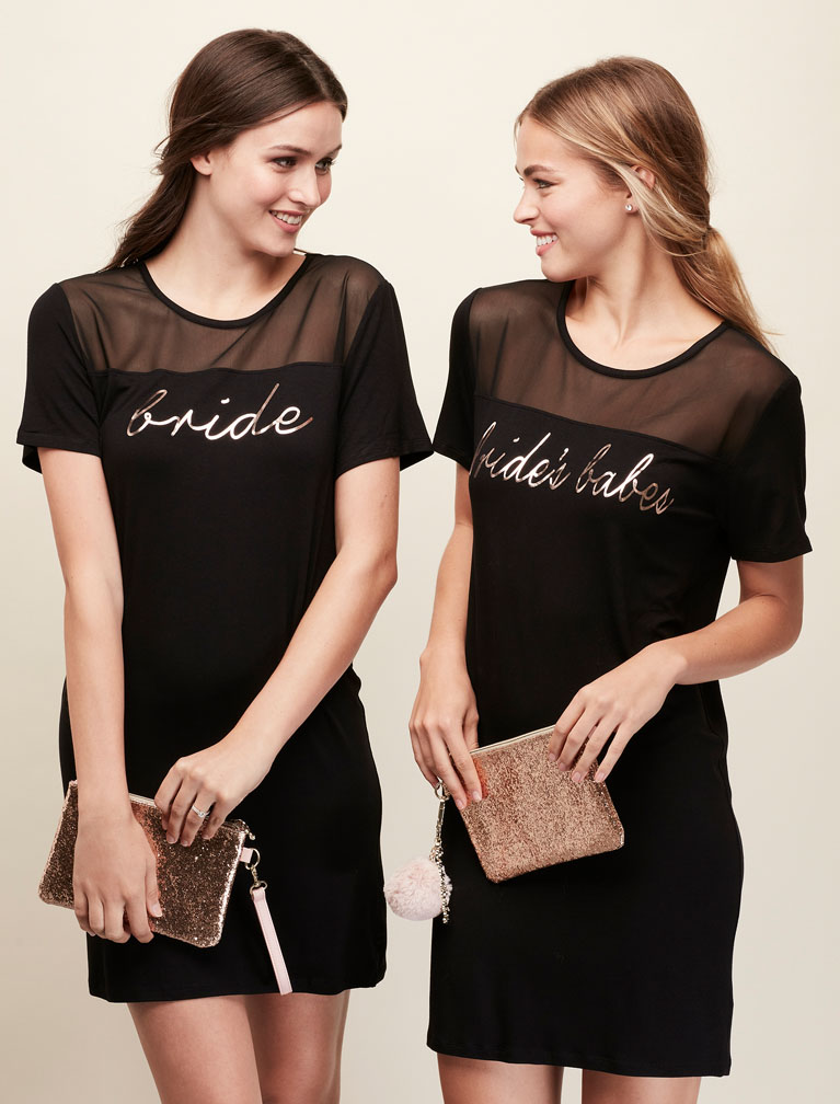 Bride and Bridesmaid wearing matching black mini dresses holding glitter purses