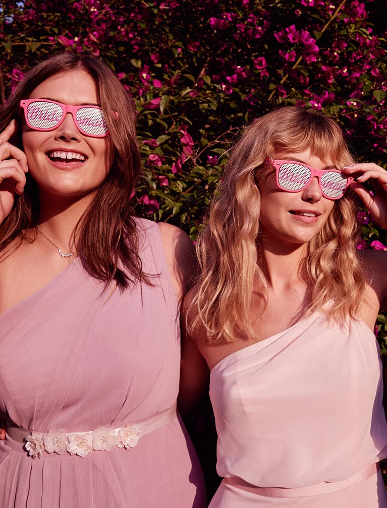 Bridesmaids wearing pink sunglasses with white lenses that say bridesmaid