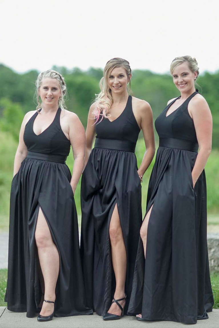 Three bridesmaids in black dresses posing with one leg out of dress