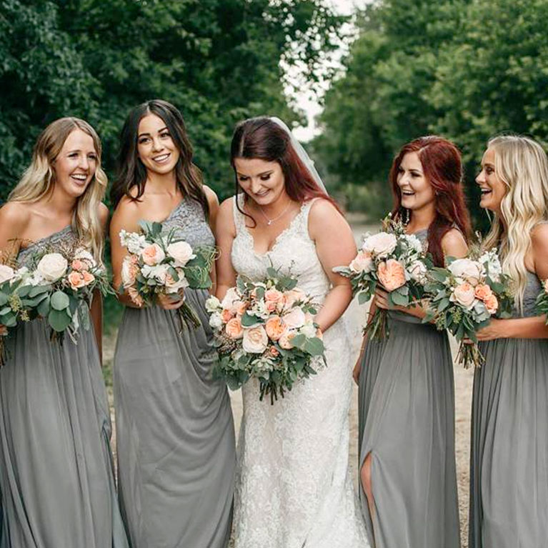 Candid shot of bride with bridesmaids in grey dresses