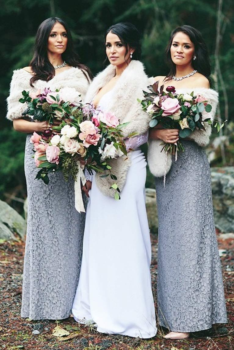 Bride posing with two bridesmaids with large bouquets and faux fur shawls