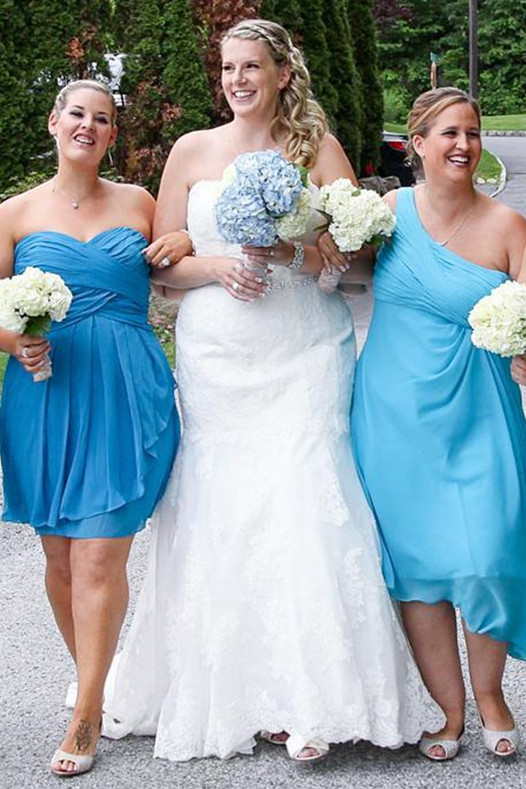 bd5a5b678ae Bridesmaids wearing short dresses linking arms with bride