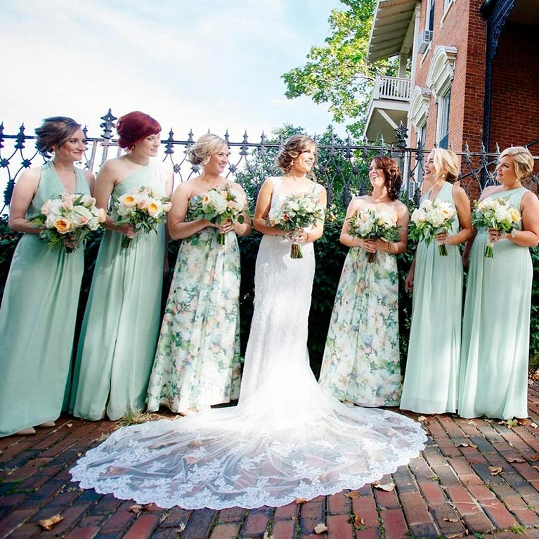 Wide angle image of bridesmaids around bride with long train displayed