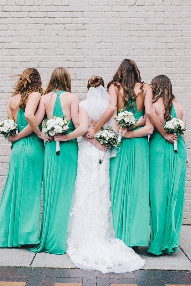 Bride and bridesmaids wrapping their arms around each other in a line from the back with bouquets and green dresses