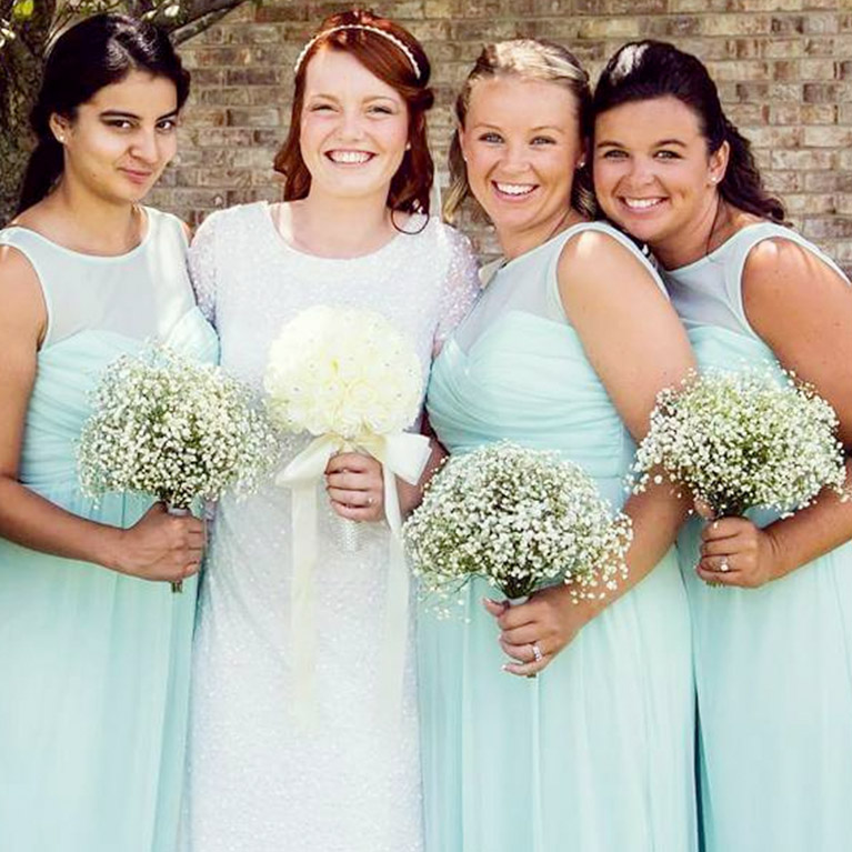 Bride posing closely to bridesmaids with baby's breath bouquets