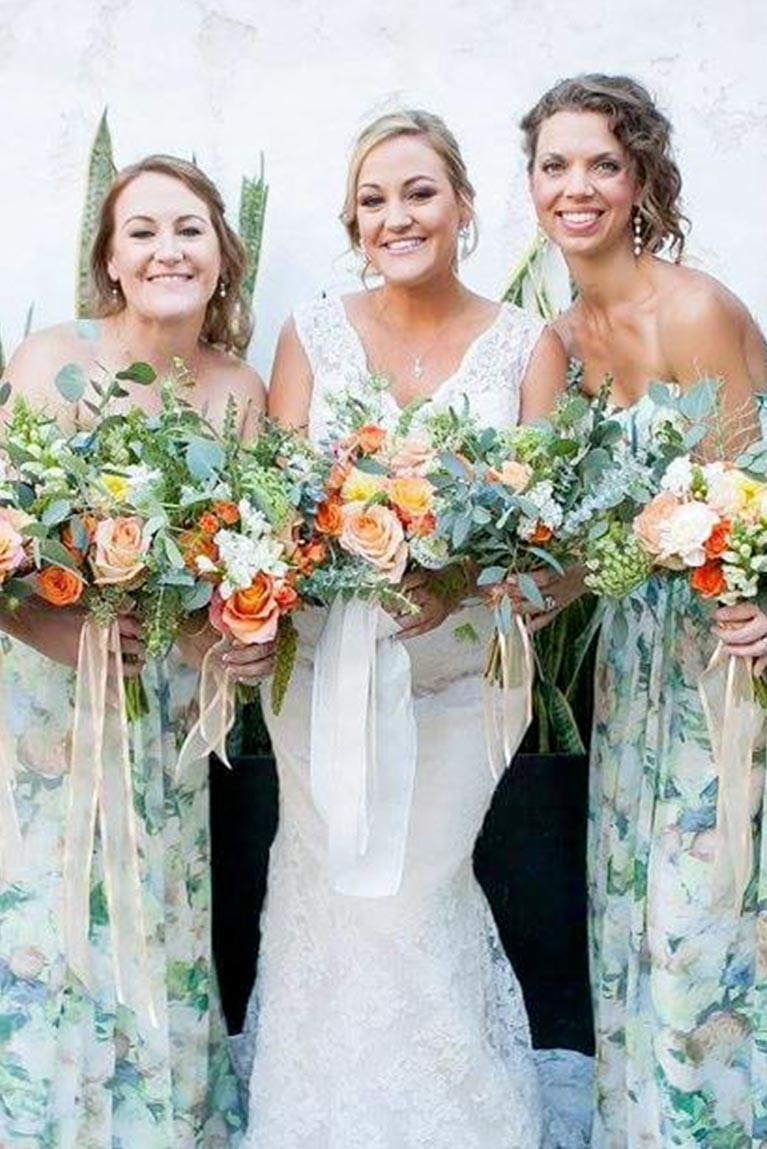 Bride and bridesmaids in printed green dresses posing closely with bouquets