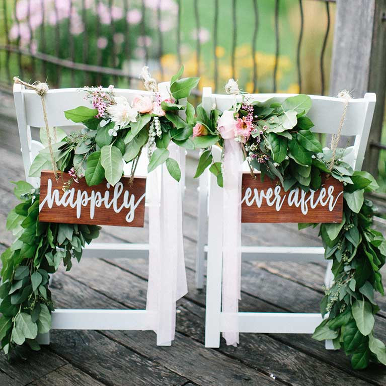 Two chairs with Happily Ever After Signs next to each other draped in leafy garland